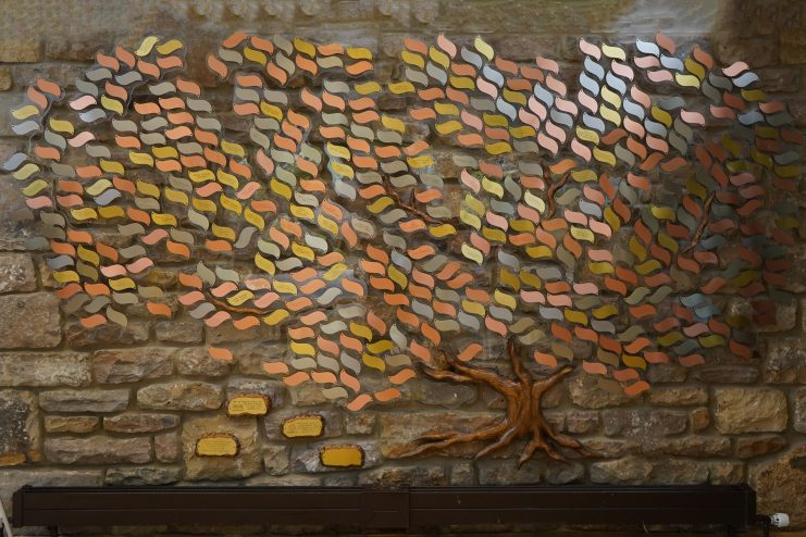 Photo of The Memory Tree, a tree against a wall in the Hospice reception, made up of gold, silver and copper leaves with inscriptions on